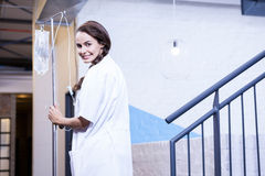 Portrait of female doctor carrying saline stand royalty free stock images