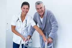 Portrait of female doctor helping senior man to walk with walker Royalty Free Stock Images