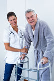 Portrait of female doctor helping senior man to walk with walker Stock Photos