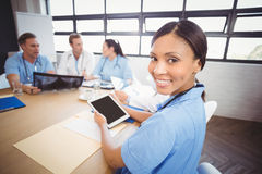 Portrait of female doctor holding digital tablet in conference room Stock Image