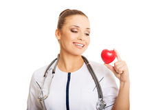 Portrait of female doctor holding heart model Stock Photo