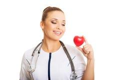Portrait of female doctor holding heart model.  stock photo