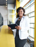 Portrait of a female doctor holding her patient chart on digital tablet in bright modern hospital Stock Photography