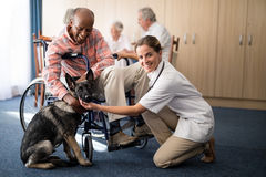 Portrait of female doctor kneeling by disabled senior man stroking puppy Stock Photos