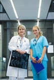 Portrait of female doctor and nurse standing in corridor. At hospital Royalty Free Stock Photo