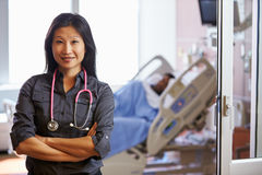Portrait Of Female Doctor With Patient In Background Stock Image