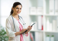 Portrait of female doctor or pharmacist with clipboard over medical background Stock Image