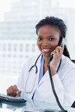 Portrait of a female doctor on the phone. In her office Stock Photo