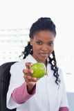 Portrait of a female doctor showing an apple. In her office Stock Photography