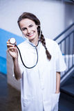 Portrait of female doctor showing stethoscope stock photo
