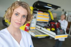 Portrait female doctor standing in front ambulance. Portrait of female doctor standing in front of ambulance Royalty Free Stock Photo