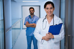 Portrait of female doctor standing with nurse in background Royalty Free Stock Photo