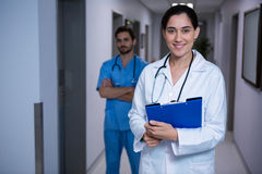 Portrait of female doctor standing with nurse in background Royalty Free Stock Photos