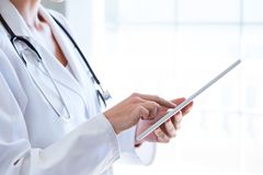 Female doctor using her digital tablet in the office. Stock Images