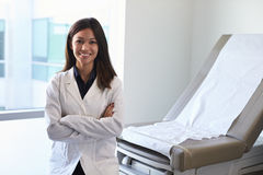 Portrait Of Female Doctor Wearing White Coat In Exam Room Stock Photography