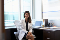 Portrait Of Female Doctor Wearing White Coat In Office Stock Images