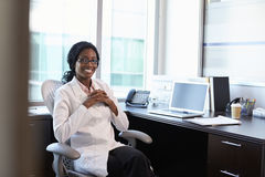Portrait Of Female Doctor Wearing White Coat In Office Stock Image
