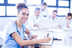 Portrait of female doctors writing on clipboard. And other doctors discussing behind in conference room Stock Images