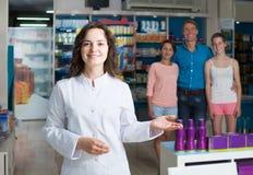 Portrait of  female druggist in white coat working in pharmacy. Portrait of glad european female druggist in white coat working in pharmacy Royalty Free Stock Photos