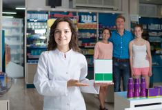 Portrait of  female druggist in white coat working in pharmacy. Portrait of glad russian  female druggist in white coat working in pharmacy Royalty Free Stock Photos