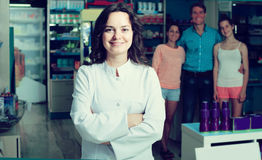 Portrait of  female druggist in white coat working in pharmacy. Portrait of glad spanish female druggist in white coat working in pharmacy Stock Photo