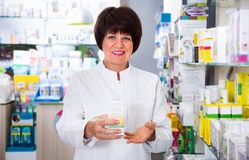 Portrait of  female druggist working in pharmacy. Portrait of cheerful  glad female druggist in white coat working in pharmacy Stock Photography