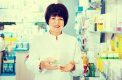 Portrait of  female druggist working in pharmacy. Portrait of cheerful  glad female druggist in white coat working in pharmacy Stock Photo