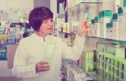 Portrait of  female druggist working in pharmacy. Portrait of diligent  positive glad female druggist in white coat working in pharmacy Stock Image