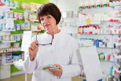 Portrait of  female druggist working in pharmacy. Portrait of diligent satisfied pleasant  female druggist in white coat working in pharmacy Royalty Free Stock Image