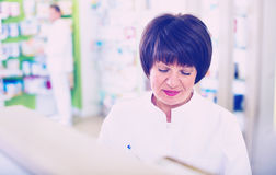 Portrait of  female druggist working in pharmacy. Portrait of diligent smiling friendly glad female druggist in white coat working in pharmacy Royalty Free Stock Image