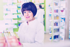 Portrait of  female druggist working in pharmacy. Portrait of diligent female druggist in white coat working in pharmacy Stock Images