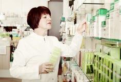 Portrait of  female druggist working in pharmacy. Portrait of  smiling positive glad female druggist in white coat working in pharmacy Stock Photos
