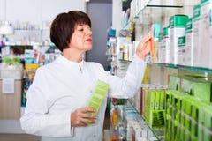Portrait of  female druggist working in pharmacy. Portrait of  smiling positive glad female druggist in white coat working in pharmacy Royalty Free Stock Photos