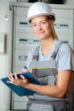 Portrait female electrician with clipboard. Portrait of female electrician with clipboard Stock Photo