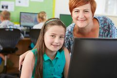 Female Elementary Pupil In Computer Class With Teacher. Portrait Of Female Elementary Pupil In Computer Class With Teacher Royalty Free Stock Photos