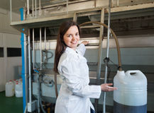 Portrait of female engineer filling containers with olive oil Stock Image