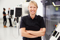 Portrait Of Female Engineer Operating CNC Machinery Royalty Free Stock Image