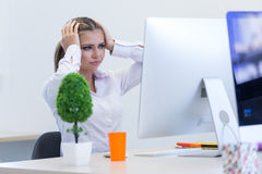 Portrait of female entrepreneur sitting in the office while doin Royalty Free Stock Images