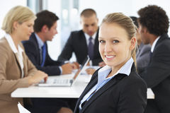 Portrait Of Female Executive With Office Meeting In Background Stock Photography