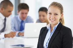 Portrait Of Female Executive With Office Meeting In Background Stock Photos
