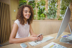 Portrait of female executive sitting at desk and using mobile phone Stock Photos