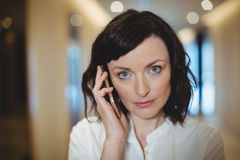 Portrait of female executive talking on mobile phone in corridor Royalty Free Stock Images