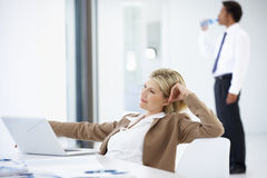 Portrait Of Female Executive Using Laptop Relaxing In Office Stock Photo