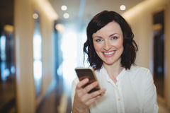 Portrait of female executive using mobile phone in corridor Royalty Free Stock Image