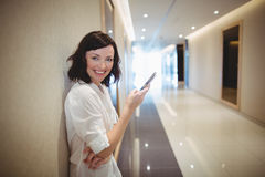 Portrait of female executive using mobile phone in corridor Stock Photography