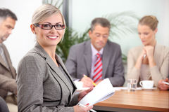 Portrait of female executive wearing glasses. Portrait of smiling female executive with her colleagues in the background Royalty Free Stock Photo