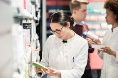 Portrait of a female experienced pharmacist reading indications. Portrait of a female experienced pharmacist reading the indications from the package of a new stock photography