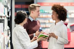 Portrait of a female experienced pharmacist reading the indications. From the package of a new pharmaceutical product during work in a contemporary drugstore stock photos
