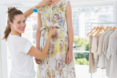 Portrait of a female fashion designer measuring model Royalty Free Stock Photography