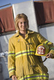 Portrait Of A Female Firefighter Holding Helmet. Portrait of a happy middle aged female firefighter holding helmet with fire brigade in the background royalty free stock photo